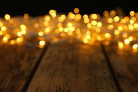 Verschwommene Sicht auf leuchtende Weihnachtsbeleuchtung auf Holztisch Standard-Bild