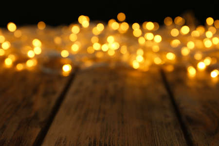 Vista borrosa de brillantes luces de Navidad en mesa de madera Foto de archivo
