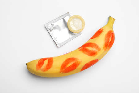 Condom and banana with lipstick kiss marks on white background, top view. Safe sex