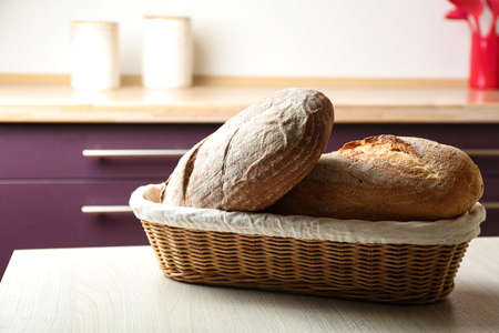 Wicker basket with loaves of tasty fresh bread on wooden table in kitchen