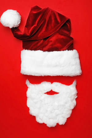 Santa Claus hat with white beard on red background, flat lay