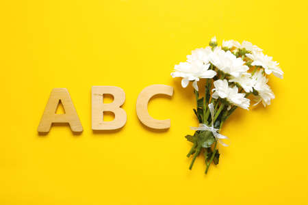 Flat lay composition with flowers and letters on yellow background. Teacher's day