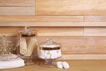 Composition of glass jar with cotton pads on table near wooden wall. Space for text 写真素材 - 129572684