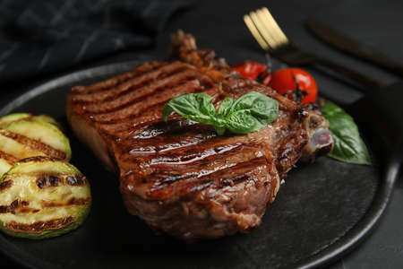 Board with grilled meat steak on black table, closeup