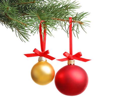 Kerstballen die op dennenboomtak hangen tegen witte achtergrond Stockfoto
