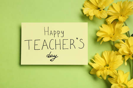 Paper with inscription HAPPY TEACHER'S DAY and flowers on light green background, flat lay