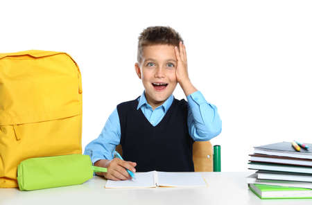 Emotional little boy in uniform with school stationery at desk against white background Stock fotó
