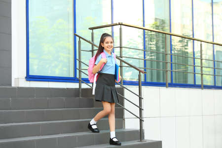 Cute little girl in school uniform with backpack and stationery on stairs outdoors