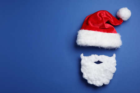 Santa Claus hat and beard on blue background, flat lay. Space for text