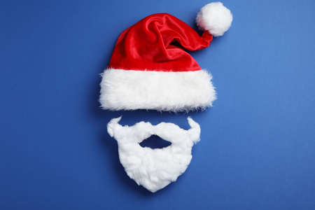Santa Claus hat and beard on blue background, flat lay Stockfoto