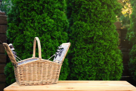 Wicker picnic basket on wooden table in park. Space for text 스톡 콘텐츠