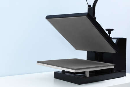 Heat press machine on table against light background
