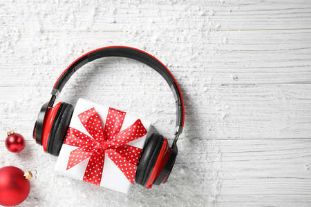 Flat lay composition with headphones on white wooden background, space for text. Christmas music concept Stockfoto