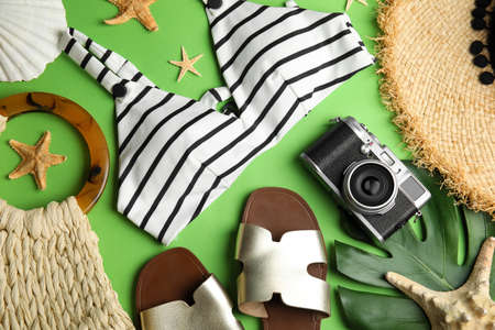 Flat lay composition with beach objects on green background