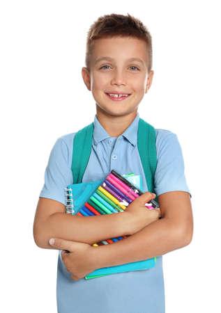 Schattige kleine jongen in schooluniform met rugzak en briefpapier op witte achtergrond Stockfoto