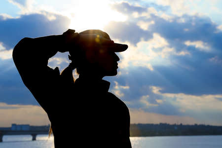 Female soldier in uniform saluting outdoors. Military service