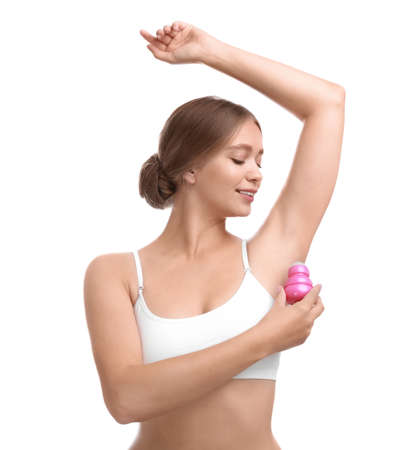 Young woman applying deodorant to armpit on white background