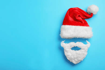 Santa Claus hat and beard on light blue background, flat lay. Space for text Stockfoto