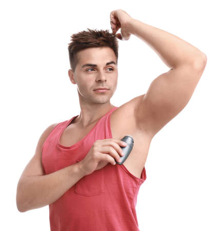 Young man applying deodorant to armpit on white background