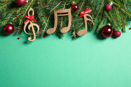 Flat lay composition with Christmas decor and music notes on light green background, space for text Stock Photo
