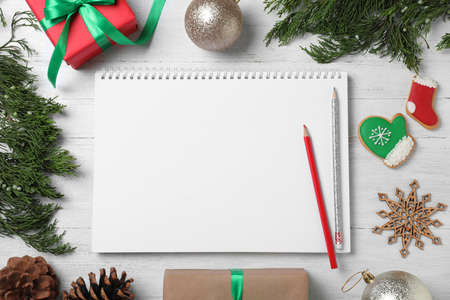 Flat lay composition with empty notebook and Christmas decorations on white wooden table, space for text. Writing letter to Santa Claus