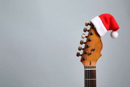 Guitar with Santa hat on grey background, space for text. Christmas music Stock Photo - 129573715