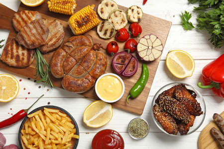 Flat lay composition with barbecued meat and vegetables on white wooden table
