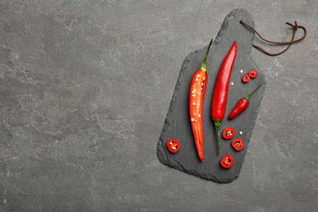 Slate plate with red hot chili peppers on grey table, top view. Space for text Reklamní fotografie