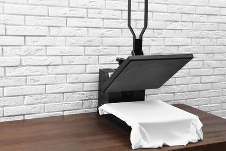 Heat press machine with t-shirt on wooden table near white brick wall. Space for text Фото со стока