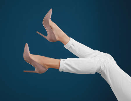 Woman in elegant shoes on dark blue background Archivio Fotografico - 129576146