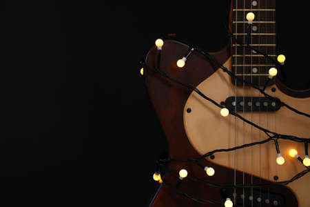Guitar with golden lights on black background, space for text. Christmas music Stock Photo