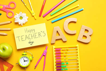 Flat lay composition of card with inscription HAPPY TEACHERS DAY and stationery on orange background