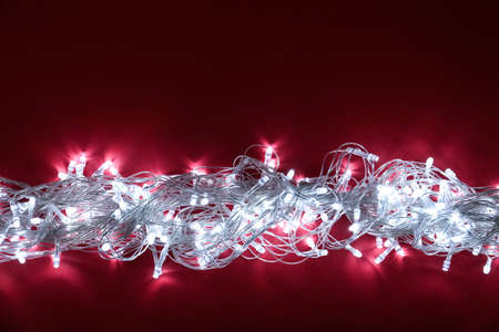 Glowing Christmas lights on burgundy background, top view. Space for text