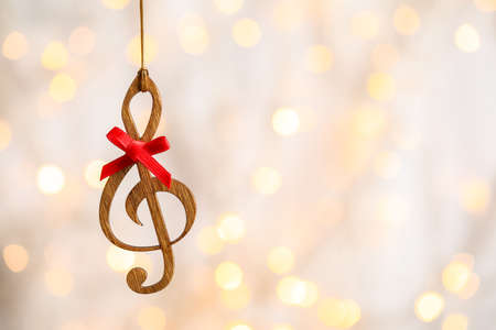 Wooden treble clef against blurred lights, space for text. Christmas music