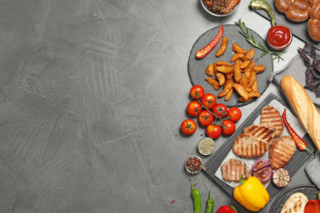 Flat lay composition with barbecued meat and vegetables on grey table. Space for text 스톡 콘텐츠