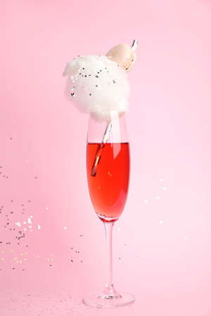 Cocktail with cotton candy in glass on pink background