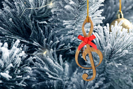 Fir tree with wooden treble clef and decor, closeup view. Christmas music Stock Photo