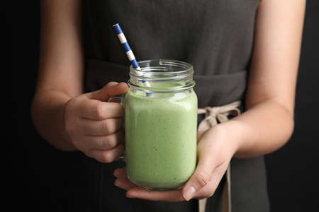 Young woman holding mason jar of tasty avocado smoothie with straw on black background, closeup