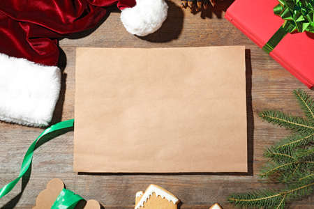 Flat lay composition with empty card and Christmas decorations on wooden table, space for text. Writing letter to Santa Claus