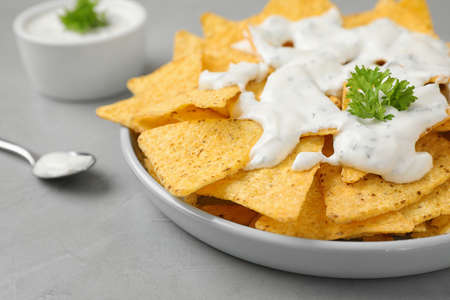 Plate of Mexican nacho chips with sauce on grey table, closeup