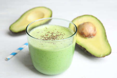 Glass of tasty avocado smoothie with chia seeds on white wooden table