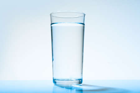 Glass of water on blue background. Refreshing drink