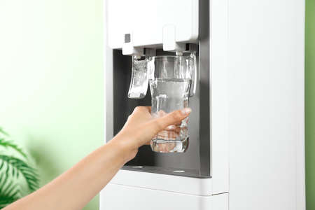 Woman filling glass from water cooler indoors, closeup. Refreshing drink Imagens