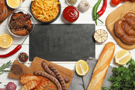 Flat lay composition with barbecued meat and vegetables on white wooden table. Space for text