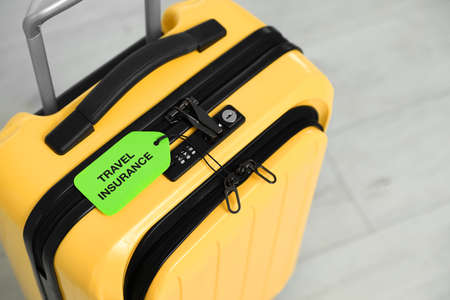 Above view of yellow suitcase with TRAVEL INSURANCE label indoors, closeup