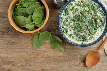 Tasty spinach dip on wooden table, flat lay