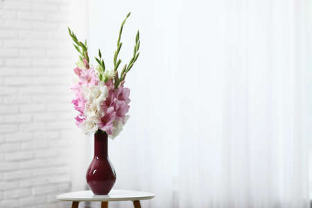 Vase with beautiful gladiolus flowers on wooden table indoors. Space for text