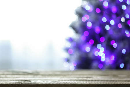 Blurred view of beautiful Christmas tree with purple lights near window indoors, focus on wooden table. Space for text