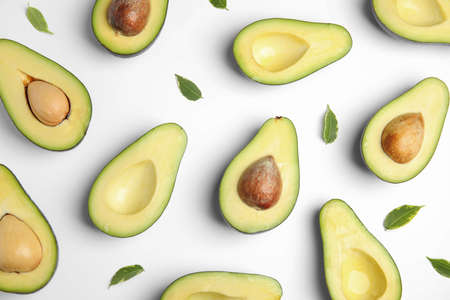 Cut fresh ripe avocados and leaves on white background, top view