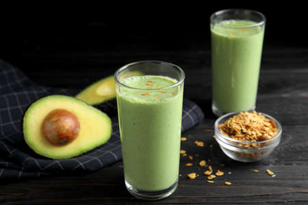 Glasses of tasty smoothie with avocado and oatmeal on black wooden table